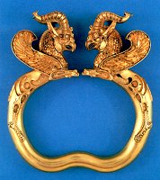A pair of gold armlets with terminals in the shape of horned griffins